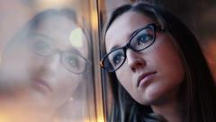 Young, sad woman standing by the window HD - stock footage