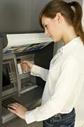 Side profile of a businesswoman using an ATM Stock Photos