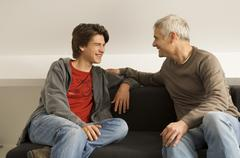 Mature man with his son sitting on a couch and gossiping Stock Photos
