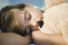 Close-up of a girl sleeping with a teddy bear - stock photo