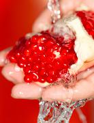 Ripe red pomegranate in her hand in water Stock Photos