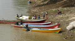 People and small boats at the shore of the Ayeyarwady river, Myanmar, Burma Stock Footage