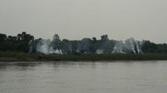 Smoke from the farm land next to the Ayeyarwady river side, Myanmar, Burma Stock Footage