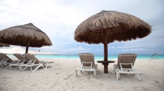 Sun umbrellas and beach beds on coastline Stock Footage