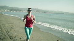 Young, pretty woman jogging along the city beach HD - stock footage