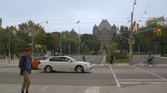 Pedestrians cross intersection infront of Queens Park in Toronto Stock Footage