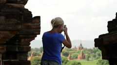 Blond european woman makes a photo from the Pagodas in Bagan, Myanmar, Burma Stock Footage