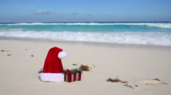 Santa Hat and present box on tropical beach Stock Footage