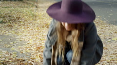 Young woman throws leaves up in the air and they float down on top of her Stock Footage