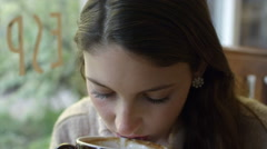 Close up of a young woman sipping her coffee in a cafe Stock Footage