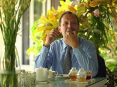 Happy businessman spreading jam on toast during breakfast in the garden. NTSC Stock Footage