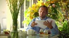 Handsome businessman looking through the documents after morning breakfast HD Stock Footage
