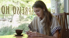Young woman sits in a cafe and texts on her cell phone while drinking coffee Stock Footage