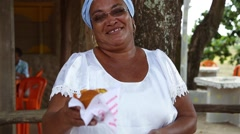 A Brazilian woman of African descent, smiling, with the traditional food Acaraje Stock Footage