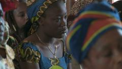 Pretty young woman in colorful dress in African church Stock Footage