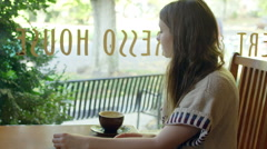 A young woman sitting at a table in a cafe stands up puts on her coat and leaves Stock Footage