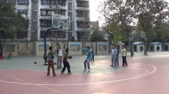 Kids play basketball on the playground in a school, coaching by a teacher - stock footage