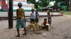 Kids playing with a coconut tree leaf in Pathein, Myanmar, Burma Stock Footage