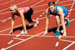 Athletes at starting line on race track Stock Photos