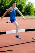 Male athlete jumping hurdle Stock Photos