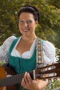 Bavarian woman in dirndl smiling while playing guitar at the lake Stock Photos