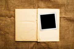 Old open book with photo frame - stock photo