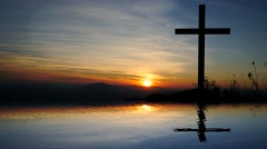 water reflection of religious cross in landscape at sunset - stock footage