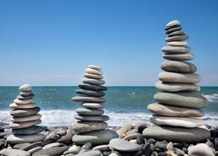 Three pyramids of stones for meditation lying on seacoast Stock Photos