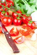Fresh tomatoes, rucola, garlic and old knife Stock Photos