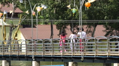 Boy and girls walking on a bridge in Pathein, Myanmar, Burma Stock Footage