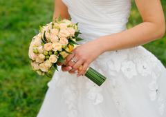 Wedding bouquet in hands of the bride with roses cream Stock Photos