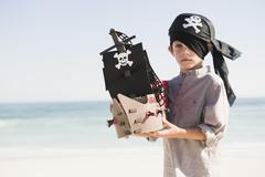 Boy in pirate costume playing with a toy boat Stock Photos