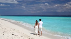 Young beautiful newlyweds in love holding hands and walking on tropical  beach Stock Footage