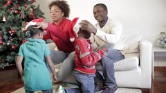 African parents putting to her sons the christmas hat - stock footage