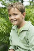 Boy holding a blade of grass in his mouth and smiling Stock Photos