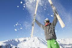 Young man holding his skis above his head - stock photo