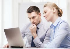 serious business couple with laptop computer - stock photo