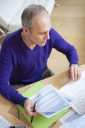 Man holding tax forms and using a laptop - stock photo