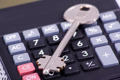 Black calculator with a key isolated on a white background Stock Photos