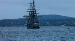 Tall ship leaving harbor at dusk Stock Footage