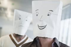 Two businessmen wearing paper bags of happy and sad faces - stock photo