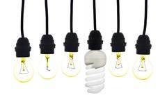 A light bulb with low consumption light bulbs hanging between - stock photo