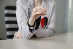 Female financial advisor holding a car key in an office Stock Photos
