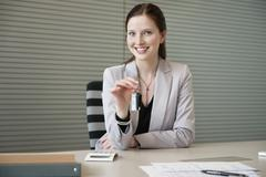Female financial advisor holding a car key in an office - stock photo