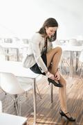 Businesswoman adjusting her sandal - stock photo