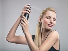 Young woman using hairspray - stock photo