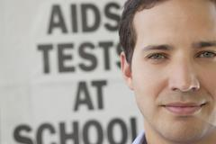 Close-up of a man in front of AIDS awareness poster Stock Photos