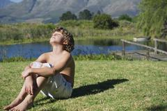 Shirtless little boy sitting with his eyes closed against mountain Stock Photos