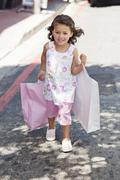 Cute little girl walking with shopping bags in hands Stock Photos