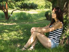 Young woman sitting on a tree Stock Photos